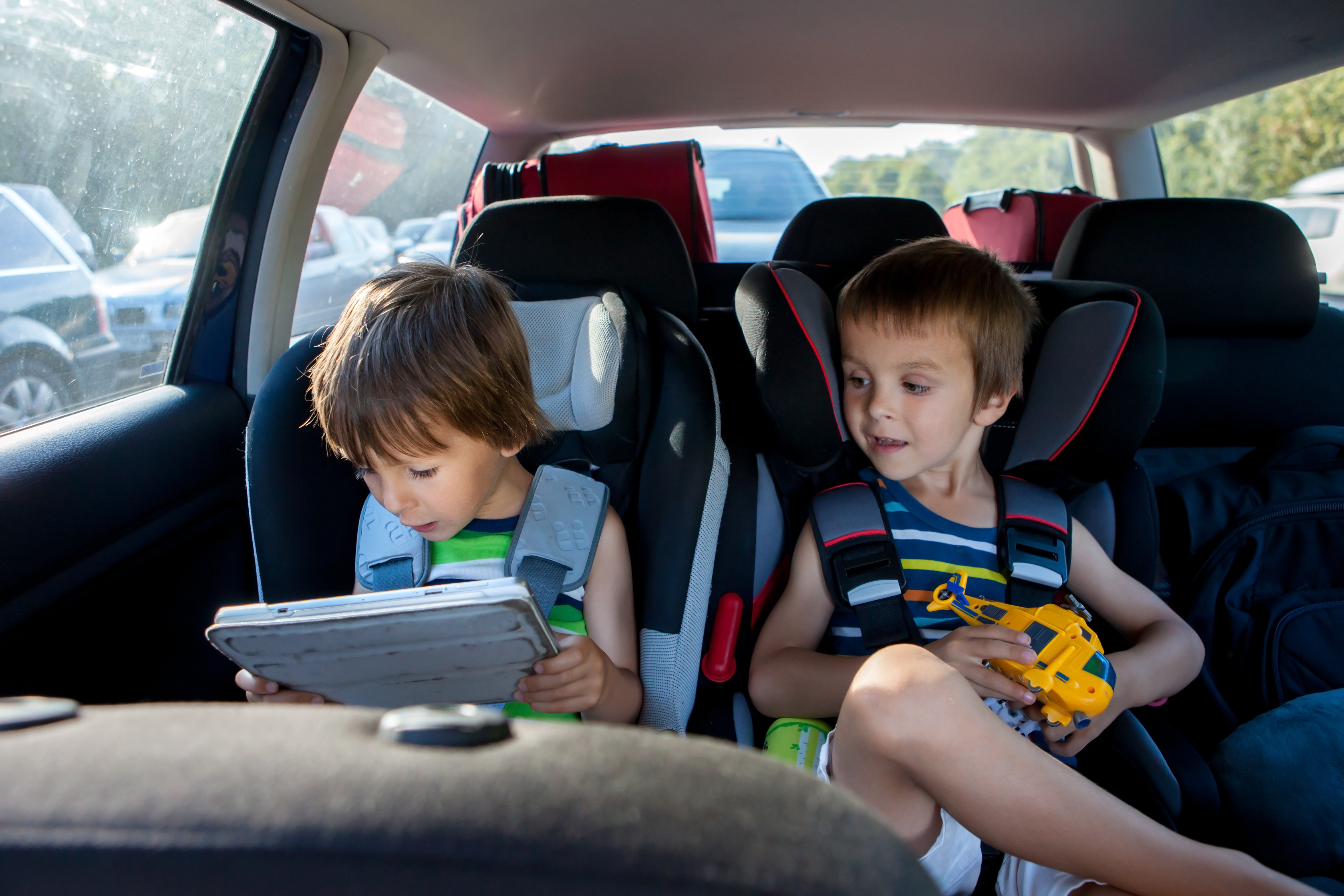 Two boy in children car seats, traveling by car and playing with